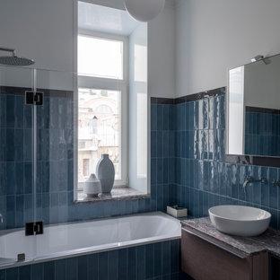 На фото: ванная комната в стиле неоклассика (современная классика) с плоскими фасадами, фасадами цвета дерева среднего тона, накладной ванной, душем над ванной, синей плиткой, белыми стенами, душевой кабиной, настольной раковиной, открытым душем, серой столешницей и фартуком