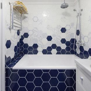 На фото: главные ванные комнаты в современном стиле с ванной в нише, душем над ванной, монолитной раковиной и синим полом