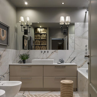 This is an example of a mid-sized transitional master bathroom in Moscow with beige cabinets, an alcove tub, white tile, porcelain tile, grey walls, porcelain floors, white floor, flat-panel cabinets, a bidet and a vessel sink.