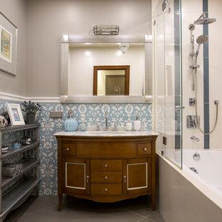 Идея дизайна: главная ванная комната среднего размера в стиле современная классика с фасадами цвета дерева среднего тона, ванной в нише, душем над ванной, синей плиткой, серыми стенами, врезной раковиной, мраморной столешницей и серым полом