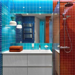 Ispirazione per una stanza da bagno con doccia design di medie dimensioni con ante lisce, ante bianche, doccia aperta, WC sospeso, piastrelle arancioni, piastrelle di vetro, pareti blu, pavimento in gres porcellanato, lavabo integrato, top in superficie solida, pavimento grigio, doccia con tenda, top bianco, un lavabo e mobile bagno sospeso