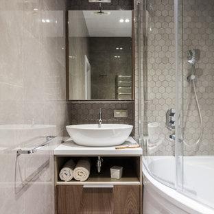 Пример оригинального дизайна: маленькая ванная комната в современном стиле с плоскими фасадами, фасадами цвета дерева среднего тона, угловым душем, серой плиткой, душевой кабиной, настольной раковиной, серым полом, душем с распашными дверями, белой столешницей и встроенной тумбой