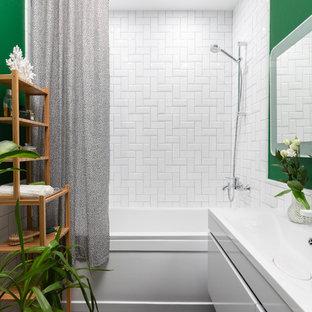 На фото: главная ванная комната в современном стиле с плоскими фасадами, белыми фасадами, ванной в нише, зелеными стенами, черным полом, шторкой для ванной, душем над ванной, белой плиткой, монолитной раковиной и белой столешницей с