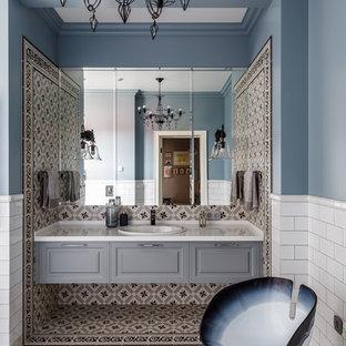 Новые идеи обустройства дома: ванная комната в классическом стиле с фасадами с выступающей филенкой, серыми фасадами, разноцветной плиткой, белой плиткой, синими стенами, накладной раковиной, разноцветным полом и белой столешницей