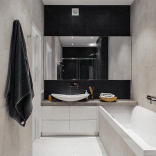 Diseño de cuarto de baño bohemio, pequeño, con armarios con paneles lisos, puertas de armario blancas, sanitario de pared, baldosas y/o azulejos negros, baldosas y/o azulejos beige, baldosas y/o azulejos blancos, baldosas y/o azulejos de cerámica, paredes blancas, suelo de baldosas de cerámica, lavabo encastrado y encimera de cemento
