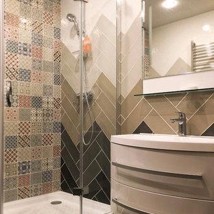 На фото: ванная комната в современном стиле с разноцветной плиткой, душевой кабиной и монолитной раковиной с