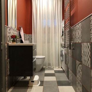 Aménagement d'une salle d'eau classique avec un placard à porte plane, des portes de placard noires, un WC à poser, un carrelage gris, des carreaux de béton, un mur rouge, un sol en carreaux de ciment, un plan vasque, un sol multicolore et un plan de toilette blanc.
