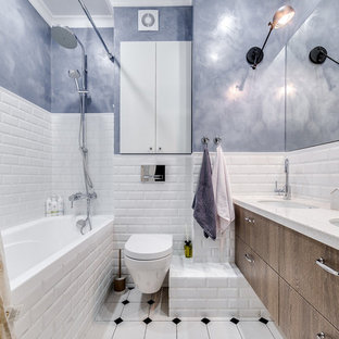 Small scandinavian family bathroom in Saint Petersburg with flat-panel cabinets, a shower/bath combination, a wall mounted toilet, white tiles, ceramic tiles, ceramic flooring, a submerged sink, solid surface worktops, white floors, a shower curtain, medium wood cabinets, an alcove bath, blue walls and white worktops.