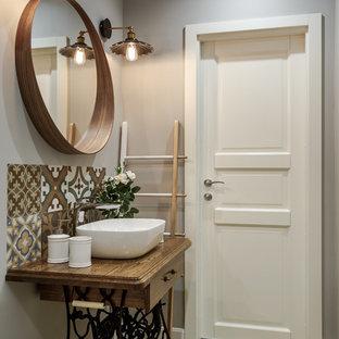Skandinavisches Badezimmer mit braunen Fliesen, beigefarbenen Fliesen, grauer Wandfarbe, Aufsatzwaschbecken, Waschtisch aus Holz, brauner Waschtischplatte, hellbraunen Holzschränken, verzierten Schränken, hellem Holzboden und beigem Boden in Moskau