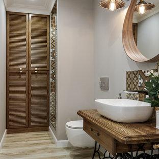 Идея дизайна: ванная комната в скандинавском стиле с фасадами цвета дерева среднего тона, инсталляцией, серыми стенами, душевой кабиной, настольной раковиной, столешницей из дерева, коричневой столешницей, фасадами островного типа, душем в нише, бежевой плиткой, коричневой плиткой, светлым паркетным полом, бежевым полом и душем с распашными дверями