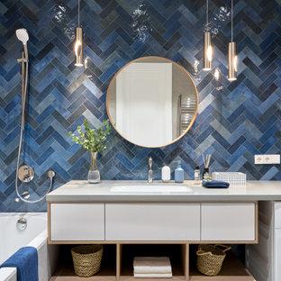 Стильный дизайн: главная ванная комната со стиральной машиной в современном стиле с плоскими фасадами, белыми фасадами, душем над ванной, синей плиткой, врезной раковиной, серой столешницей и тумбой под одну раковину - последний тренд