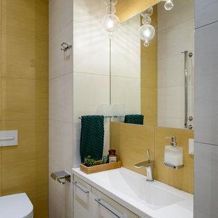 Пример оригинального дизайна: ванная комната в современном стиле с инсталляцией, столешницей из искусственного камня, плоскими фасадами, белыми фасадами, желтой плиткой, желтыми стенами, консольной раковиной, коричневым полом и белой столешницей