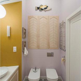 Новый формат декора квартиры: ванная комната в стиле фьюжн с писсуаром, фиолетовыми стенами, настольной раковиной, серым полом, белой столешницей, плоскими фасадами и светлыми деревянными фасадами