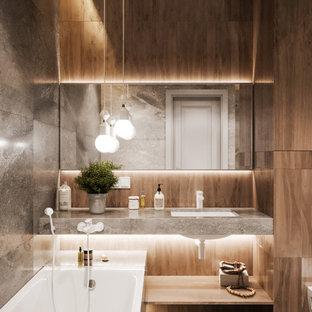 Foto de cuarto de baño con ducha, contemporáneo, de tamaño medio, con bañera encastrada sin remate, ducha empotrada, sanitario de pared, baldosas y/o azulejos grises, baldosas y/o azulejos de porcelana, paredes grises, suelo de baldosas de porcelana, lavabo bajoencimera, encimera de azulejos, suelo gris y encimeras grises