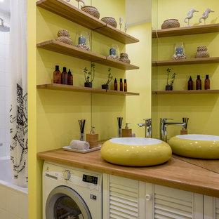 На фото: маленькая главная ванная комната в современном стиле с фасадами с филенкой типа жалюзи, белыми фасадами, ванной в нише, желтыми стенами, полом из галечной плитки, накладной раковиной, столешницей из дерева, белым полом и бежевой столешницей с
