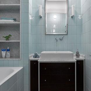 На фото: главная ванная комната в скандинавском стиле с плоскими фасадами, черными фасадами, ванной в нише, синей плиткой, настольной раковиной, бежевым полом и белой столешницей