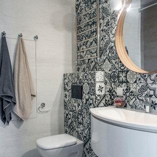 Создайте стильный интерьер: ванная комната в скандинавском стиле с белыми фасадами, инсталляцией, черно-белой плиткой, цементной плиткой, серыми стенами, душевой кабиной, подвесной раковиной, серым полом и белой столешницей - последний тренд