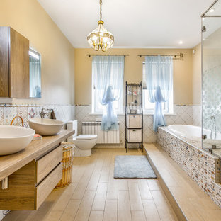 Inspiration for a large eclectic master multicolored tile light wood floor drop-in bathtub remodel in Other with flat-panel cabinets, light wood cabinets, a two-piece toilet, beige walls, a vessel sink and wood countertops
