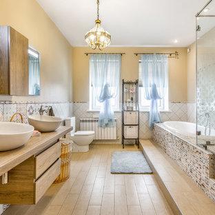 Großes Eklektisches Badezimmer En Suite mit flächenbündigen Schrankfronten, hellen Holzschränken, Einbaubadewanne, Wandtoilette mit Spülkasten, farbigen Fliesen, beiger Wandfarbe, Aufsatzwaschbecken, Waschtisch aus Holz und hellem Holzboden in Sonstige