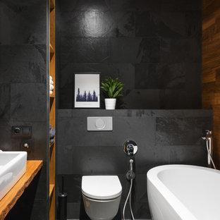 Idéer för ett litet industriellt brun en-suite badrum, med ett fristående badkar, en vägghängd toalettstol, svart kakel, ett fristående handfat, träbänkskiva, svart golv, öppna hyllor och svarta väggar