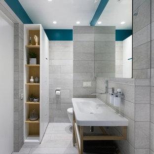 На фото: ванная комната в современном стиле с открытыми фасадами, инсталляцией, серой плиткой, синими стенами, консольной раковиной и серым полом