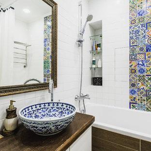 Выдающиеся фото от архитекторов и дизайнеров интерьера: маленькая главная ванная комната в средиземноморском стиле с плоскими фасадами, белыми фасадами, душем над ванной, разноцветной плиткой, керамической плиткой, белыми стенами, настольной раковиной, столешницей из дерева и коричневой столешницей
