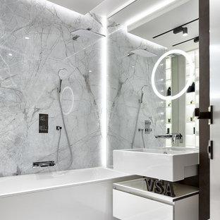 Свежая идея для дизайна: главная ванная комната в современном стиле с плоскими фасадами, белыми фасадами, ванной в нише, душем над ванной, монолитной раковиной и серым полом - отличное фото интерьера