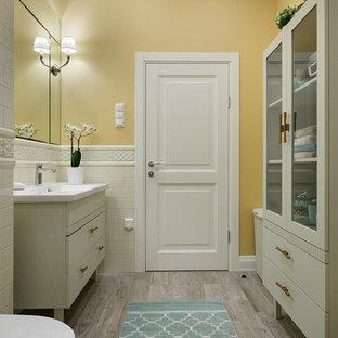 Пример оригинального дизайна: главная ванная комната среднего размера в стиле современная классика с плоскими фасадами, серыми фасадами, инсталляцией, белой плиткой, керамической плиткой, желтыми стенами, полом из керамогранита, столешницей из искусственного камня, серым полом и монолитной раковиной