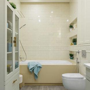 Новый формат декора квартиры: главная ванная комната среднего размера в стиле современная классика с плоскими фасадами, серыми фасадами, инсталляцией, белой плиткой, керамической плиткой, желтыми стенами, полом из керамогранита, настольной раковиной, столешницей из искусственного камня, серым полом, накладной ванной и душем над ванной