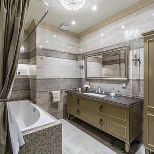 На фото: главная ванная комната среднего размера в классическом стиле с серой плиткой, керамогранитной плиткой, полом из керамогранита, врезной раковиной, столешницей из искусственного камня, коричневыми фасадами, душем над ванной, накладной ванной и шторкой для душа с