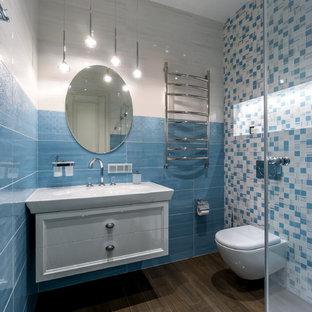 Создайте стильный интерьер: ванная комната среднего размера в современном стиле с инсталляцией, синей плиткой, белой плиткой, керамической плиткой, полом из керамогранита, фасадами с утопленной филенкой, белыми фасадами и консольной раковиной - последний тренд