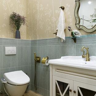 Idee per una stanza da bagno classica con ante di vetro, ante bianche, WC sospeso, piastrelle grigie, pareti beige, lavabo integrato e pavimento marrone
