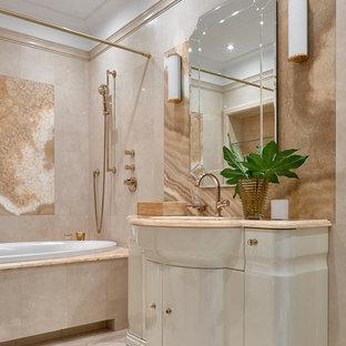 Ejemplo de cuarto de baño tradicional renovado con bañera encastrada, sanitario de una pieza, baldosas y/o azulejos beige, baldosas y/o azulejos de mármol, paredes beige, suelo de mármol, lavabo bajoencimera, encimera de ónix, suelo beige y encimeras multicolor
