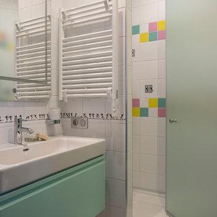 Modernes Kinderbad mit flächenbündigen Schrankfronten, türkisfarbenen Schränken, Duschnische, weißen Fliesen, farbigen Fliesen, Einbauwaschbecken, Falttür-Duschabtrennung und Wandtoilette mit Spülkasten in Moskau