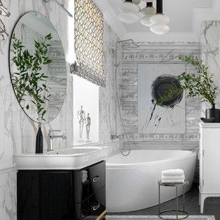 Пример оригинального дизайна интерьера: главная ванная комната в современном стиле с плоскими фасадами, черными фасадами, угловой ванной, серой плиткой, монолитной раковиной и серым полом