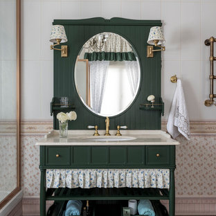 モスクワのカントリー風おしゃれな浴室 (緑のキャビネット、ベージュのタイル、セラミックタイル、磁器タイルの床、アンダーカウンター洗面器、大理石の洗面台、茶色い床、ベージュのカウンター、落し込みパネル扉のキャビネット) の写真