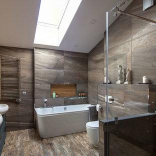 Пример оригинального дизайна: большая главная ванная комната в современном стиле с серыми фасадами, керамогранитной плиткой, полом из керамогранита, столешницей из дерева, душем с распашными дверями, фасадами с утопленной филенкой, раздельным унитазом, серой плиткой, настольной раковиной и коричневым полом