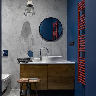 Стильный дизайн: ванная комната в современном стиле с плоскими фасадами, темными деревянными фасадами, инсталляцией, синими стенами, настольной раковиной, серым полом и белой столешницей - последний тренд