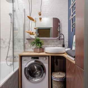 Новый формат декора квартиры: ванная комната в современном стиле с плоскими фасадами, темными деревянными фасадами, ванной в нише, душем над ванной, белой плиткой, синими стенами, настольной раковиной, столешницей из дерева, серым полом, коричневой столешницей и открытым душем