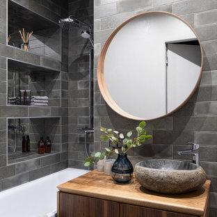 Свежая идея для дизайна: главная ванная комната в современном стиле с плоскими фасадами, фасадами цвета дерева среднего тона, серой плиткой, настольной раковиной и коричневой столешницей - отличное фото интерьера