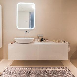 Пример оригинального дизайна: главная ванная комната в современном стиле с плоскими фасадами, белыми фасадами, ванной на ножках, бежевой плиткой, настольной раковиной, бежевым полом и белой столешницей