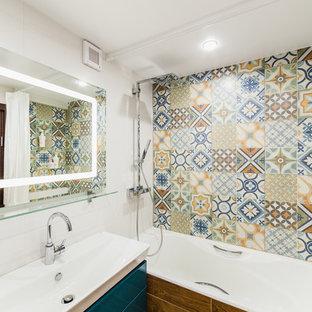 Неиссякаемый источник вдохновения для домашнего уюта: главная ванная комната в современном стиле с плоскими фасадами, синими фасадами, ванной в нише, душем над ванной, разноцветной плиткой, белыми стенами, монолитной раковиной и шторкой для душа
