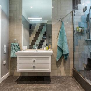 Стильный дизайн: ванная комната в современном стиле с фасадами с утопленной филенкой, белыми фасадами, душем в нише, разноцветной плиткой, серыми стенами, душевой кабиной, монолитной раковиной, коричневым полом и душем с распашными дверями - последний тренд