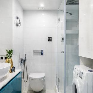 Удачное сочетание для дизайна помещения: ванная комната в современном стиле с плоскими фасадами, синими фасадами, угловым душем, инсталляцией, белой плиткой, душевой кабиной, настольной раковиной, душем с распашными дверями, полом из галечной плитки и белым полом - самое интересное для вас