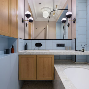 Cette image montre une salle de bain principale minimaliste de taille moyenne avec un placard avec porte à panneau encastré, des portes de placard en bois brun, une baignoire encastrée, un carrelage bleu, un sol en terrazzo, un lavabo encastré, un plan de toilette en terrazzo, un sol gris et un plan de toilette gris.
