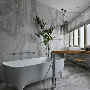 Свежая идея для дизайна: главная ванная комната среднего размера в современном стиле с ванной на ножках, серой плиткой, керамогранитной плиткой, полом из керамогранита, столешницей из дерева, настольной раковиной, серым полом и коричневой столешницей - отличное фото интерьера