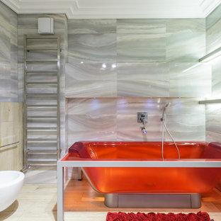 Выдающиеся фото от архитекторов и дизайнеров интерьера: ванная комната среднего размера в современном стиле с отдельно стоящей ванной, биде, светлым паркетным полом и серой плиткой