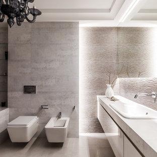 На фото: главная ванная комната в современном стиле с плоскими фасадами, белыми фасадами, накладной ванной, биде, серой плиткой, накладной раковиной, серым полом и белой столешницей с