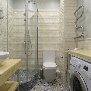 Стильный дизайн: ванная комната в современном стиле с угловым душем, унитазом-моноблоком, плиткой кабанчик, полом из керамогранита, столешницей из дерева, разноцветным полом, душем с раздвижными дверями, открытыми фасадами, бежевой плиткой, серыми стенами, душевой кабиной, настольной раковиной и бежевой столешницей - последний тренд