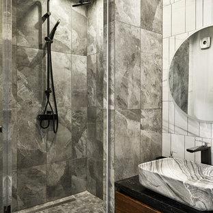 Стильный дизайн: ванная комната в современном стиле с плоскими фасадами, темными деревянными фасадами, душем в нише, серой плиткой, душевой кабиной, черной столешницей и настольной раковиной - последний тренд